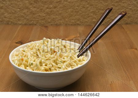 Chinese noodles on a wooden table in a white plate