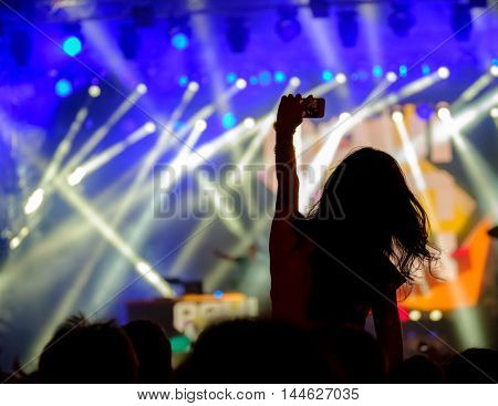 Fan using mobile device for taking pictures, videos or broadcasting at concert