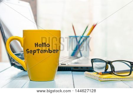 Hello September written on yellow coffee cup at teacher or student workplace. Back to school time.