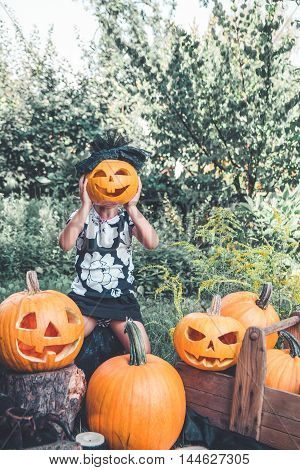 Little Girl Is Holding Halloween Pumpkin In Front Of Her Face. Child Dressed In Black Between Jack-o
