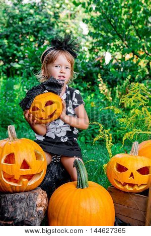 Halloween. Child Dressed In Black With Jack-o-lantern In Hand, Trick Or Treat. Little Girl Hold Pump