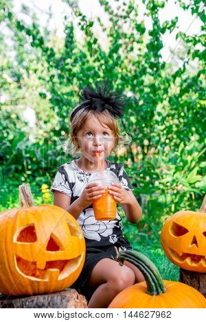 Halloween. Child Dressed In Black Drinking Pumpkin Cocktail, Trick Or Treat. Little Girl Near Jack-o