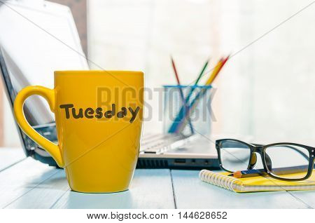 Tuesday written on yellow coffee or tea cup at wooden boards table, workplace, office sunlight morning background.