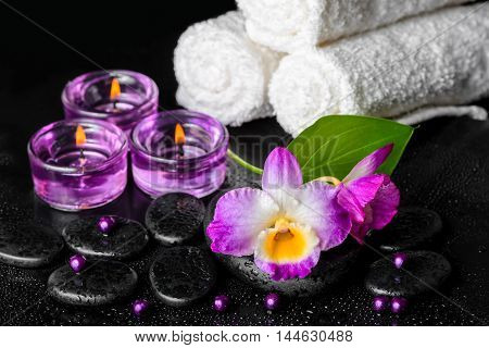 Spa Still Life Of Purple Orchid Dendrobium, Leaf With Dew, Towels, Candles And Pearl Beads  On Black