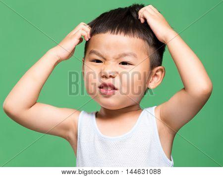 Little boy scratching his head