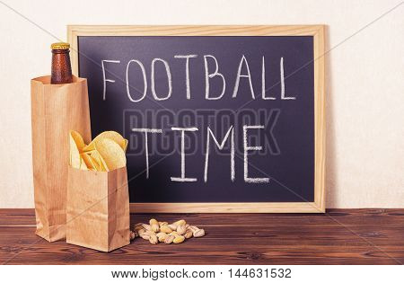 football fans concept of beer bottle in brown paper bag chips pistachio and handwriting text football time written in chalkboard over wooden background