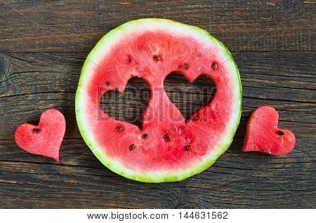 Round watermelon slice with cut in the shape of heart on dark wooden background top view
