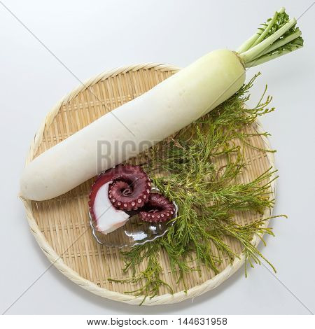 Fresh white radish on bamboo tray with raw octopus in white background