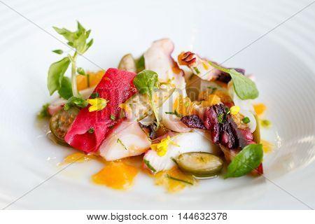 Sauteed sliced octopus smoked sunchoke breakfast radish and herbs on white platter
