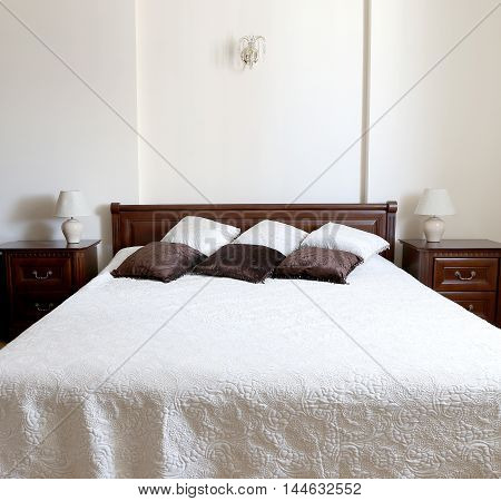 Big light bedroom in the home. Bed is decorated by brown and beige colors pillows.