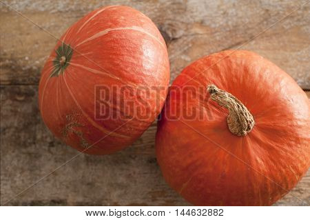 Two whole fresh orange pumpkins or seasonal squash viewed close up high angle on a wooden table