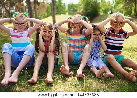Portrait of four smiling little girls with ponytails and one little blond boy sitting on grass in green park on sunny day holding fingers near eyes like glasses, pulling faces to camera.