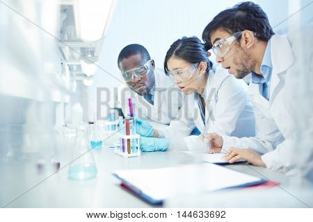 Surprised male Latin-American, male African-American and female Asian laboratory scientists in lab coats and safety goggles at test tube with purple liquid inside.