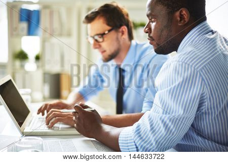 Focused African-American businessman in shirt and necktie looking as concentrated Caucasian colleague in glasses typing on laptop business strategy ideas.