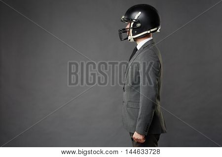 Sideview of businessman wearing tailored suit and American football helmet standing confidently facing left, isolated on black background.