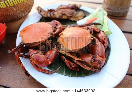 Delicious steamed red crab on white platter with herbs