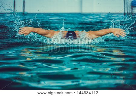 Portrait of strong professional swimmer in black cap and goggles in pool.Butterfly style.