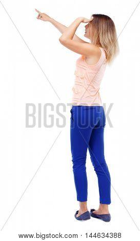 Back view of pointing woman. Isolated over white background. Blonde in blue pants looks into the distance and points a finger.