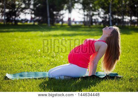 Beautiful pregnant woman in yoga pose, outdoor