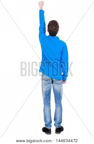 Back view of man. guy in a Curly boy in a blue sweater in pose of the superhero