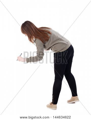 back view of writing beautiful woman. Young girl. . Isolated over white background. A young girl in a gray sweater draws felt pen bottom.