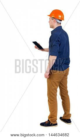 Backview of business man in construction helmet stands and enjoys tablet or using a mobile phone. man in a blue shirt and a helmet holding a tablet.