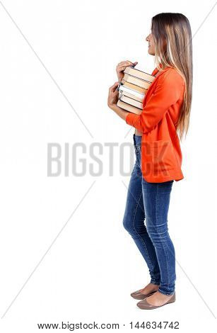 Girl comes with stack of books. side view. girl in a red jacket stands sideways with textbooks looking ahead.