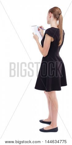 back view of stands woman takes notes in a notebook. Isolated over white background. Blonde in a short black dress takes notes in a notebook.