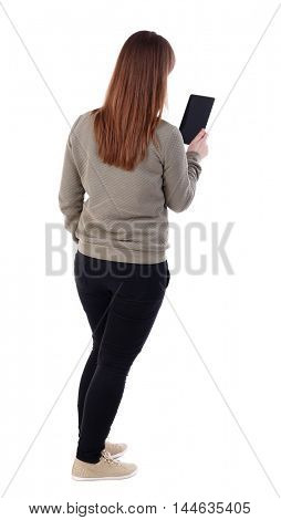 back view of standing young beautiful woman using a mobile phone. girl watching. Thrusting his hand into the pocket of a girl reading e-book.