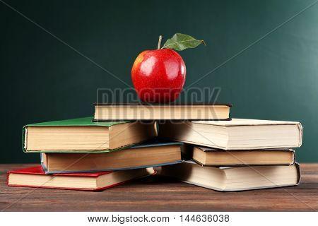 School books with apple on blackboard background