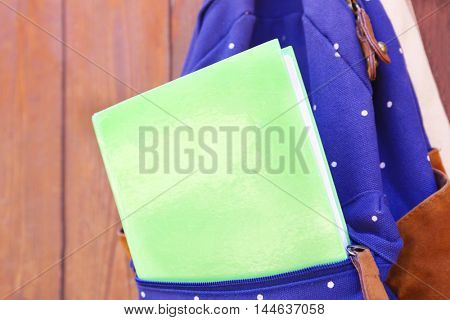 Rucksack with book hanging on wooden background