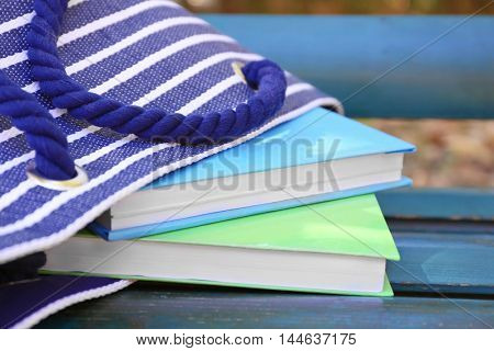 Handbag with books on wooden bench