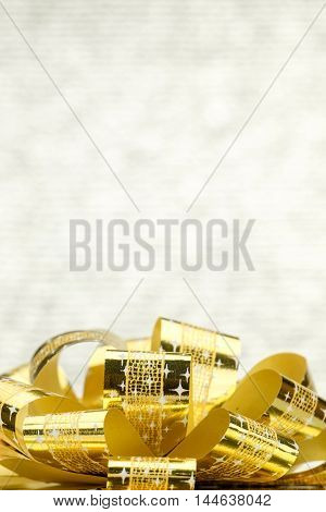 Close Up Golden Present Box With Big Bow At Bokeh White Blur Background, Leave Space On Top To Addin