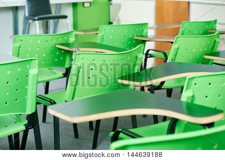 Empty classroom with green charis in a high school
