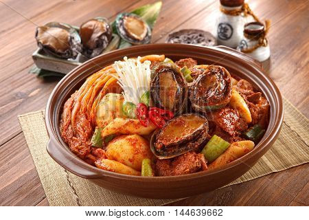 Big bowl of abalone kimchi spicy galbijjim with potatoes beef onion and mushroom on wooden korean table