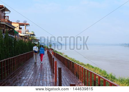 Two persons walk along a boardwalk of a small town named Chiang Khan which is next to Mekong river Thailand.