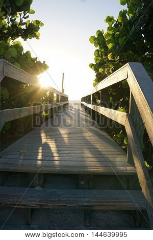 Wooden pathway leading into the sunrise at the beach