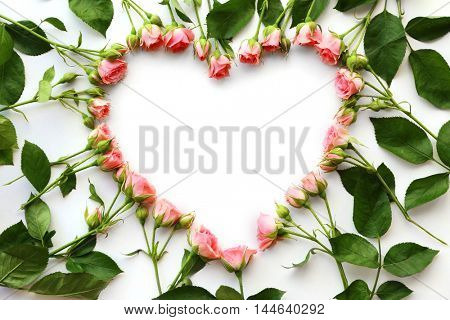 Heart frame made of beautiful flowers, top view
