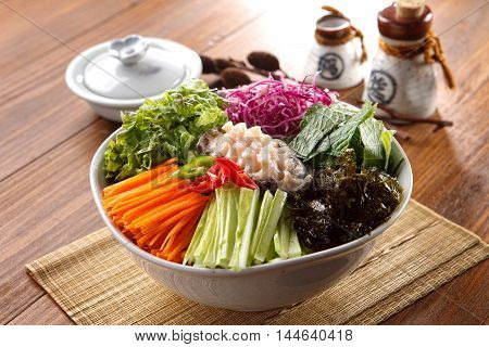 Big bowl of overture hoedeopbap with squid seaweed cucumber onion and ablone on wooden korean table