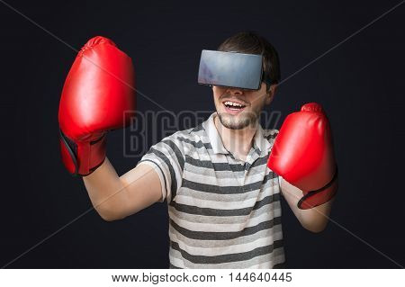 Young man is playing video game and is boxing with 3D virtual reality glasses.