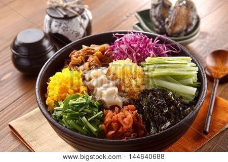 Big bowl of overture albap with squid seaweed cucumber onion and ablone on wooden korean table