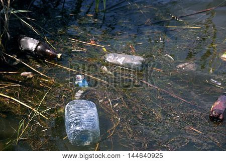 Water pollution with glass and plastic bottles