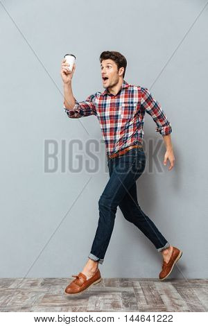 Attractive young man holding cup of takeaway coffee and running over grey background