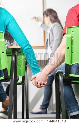 Two teenagers in class hold hands in class at their high school
