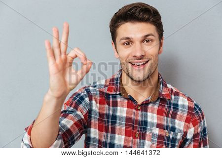 Portrait of a happy man showing okay gesture over gray background