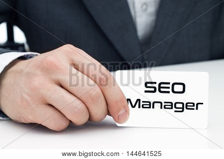 SEO manager sitting at the desk and shows his business card