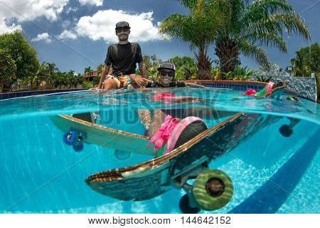 Man and Woman skateboarding  in the swimming pool