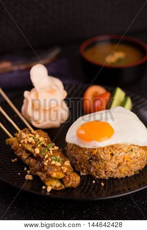 Special rice style of nasi goreng with egg roasted meat cracker and vegetables on black platter