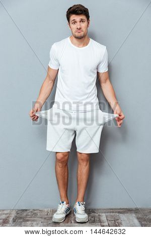 Handsome man shrugging and showing his empty pockets over gray background