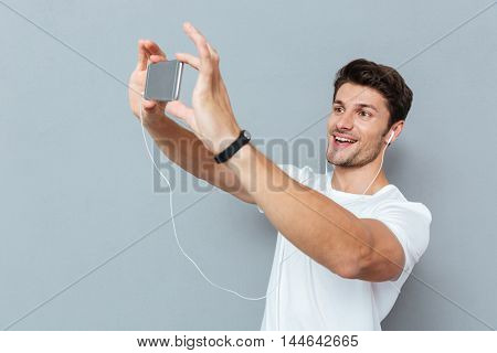 Casual young man making selfie photo on smartphone and listening music over gray background